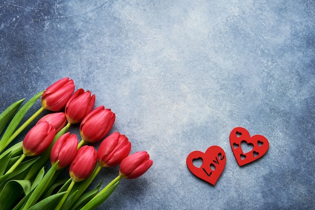 Valentine's day . bouquet of red tulips and two red hearts on a blue wall. flat lay. copy space