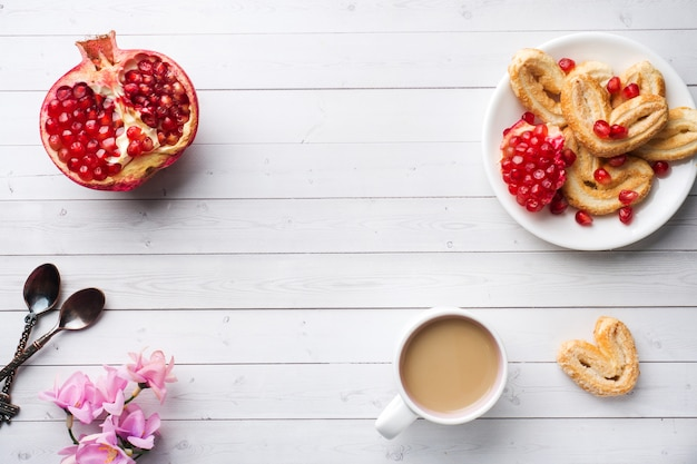 Valentine's day breakfast concept. cup of coffee and a cookies hearts on a white table. copy space, flat lay.