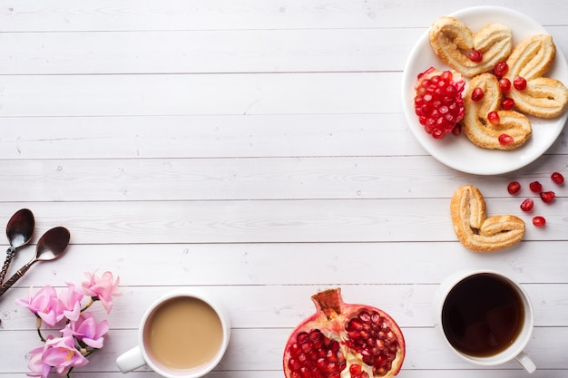 Valentine's day breakfast concept. cup of coffee and a cookies hearts on a white table two persons. copy space, flat lay.