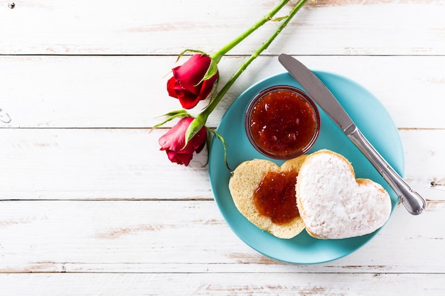 Valentine's day breakfast heart-shaped bun and berry jam, top view, copy space