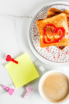 Valentine's day breakfast idea with coffee mug, toasted bread with red strawberry jam, blank paper note for congratulations with heart shaped pins, white marble background, copy space top view