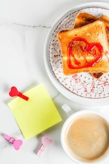 Идея завтрака в день святого валентина с кружкой кофе, поджаренным хлебом с красным клубничным джемом, запиской для поздравлений с булавками в форме сердца, белым мраморным фоном, копией пространства, вид сверху