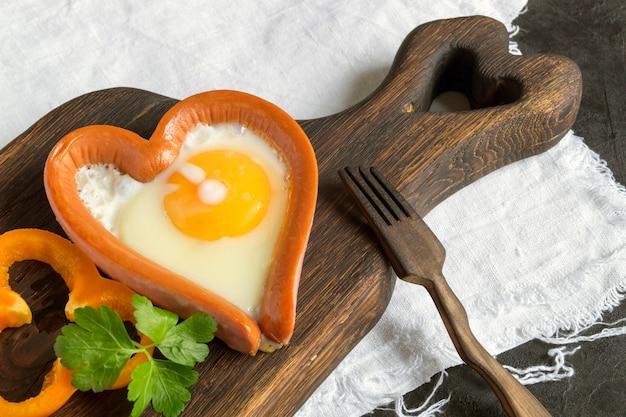 Завтрак в день святого валентина. колбаса с омлетом в форме сердца.
