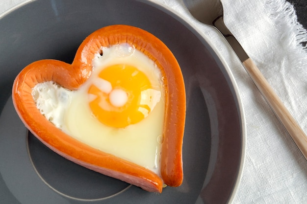 Valentine's day breakfast. sausage with scrambled egg in the shape of a heart.