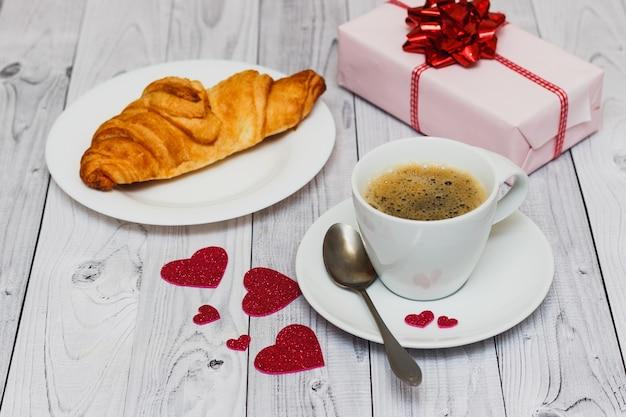 コーヒーカップ、クロワッサン、ピンクのプレゼントとバレンタインデーの朝食