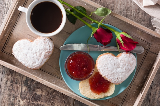 Valentine's day breakfast with coffee, heart-shaped bun, berry jam and roses on a tray, top view