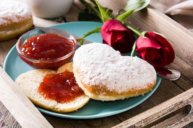 Valentine's day breakfast with coffee, heart-shaped bun, berry jam and roses on a tray