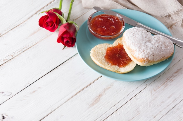 Valentine's day breakfast with coffee, heart-shaped bun, berry jam and roses