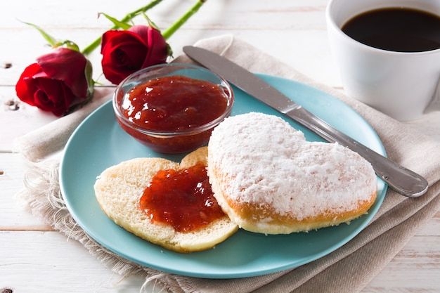 Valentine's day breakfast with coffee, heart-shaped bun and berry jam.