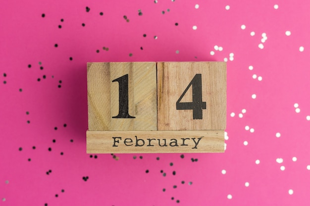Valentine's day on calendar. february 14. pink background with multicolored confetti. flat lay style