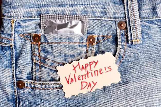 발렌타인 데이 카드와 콘돔. 데님에 인사말 카드입니다. 축하하는 동안 안전하십시오.