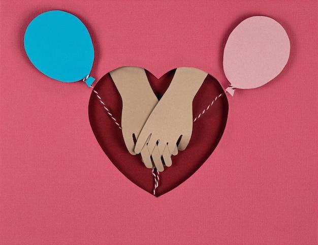 Открытка ко дню святого валентина. творческий фон вырезки из бумаги с яркими бумажными воздушными шарами и взглядом влюбленных рук. держась за руки на красном сердце. бумажное искусство на день святого валентина. вырезка из бумаги и стиль ремесла