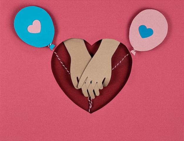 バレンタインデーカード。明るい紙風船と恋人たちの手の外観で創造的な紙カットの背景。