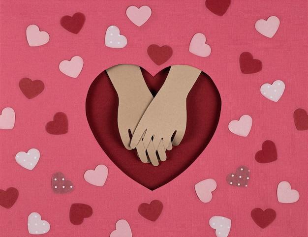 バレンタインデーカード。折り紙のハートでカットされたクリエイティブな紙と恋人たちの手の表情。