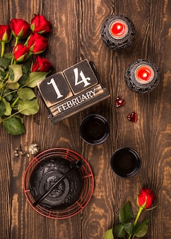 Valentine's day card. flat lay with green tea, black teapot, candles, roses and wooden calendar