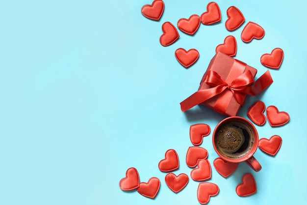 Valentine's day card. gift with red ribbon, cup of coffee and hearts on blue. top view. copyspace.