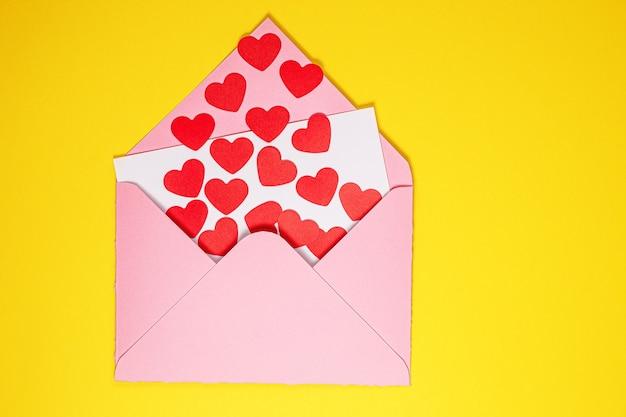 Открытка ко дню святого валентина. бумажные красные сердечки вылетают из розового бумажного конверта на желтом фоне. бумажное искусство на день святого валентина. вырезка из бумаги и стиль ремесла. место для текста. концепция дня святого валентина