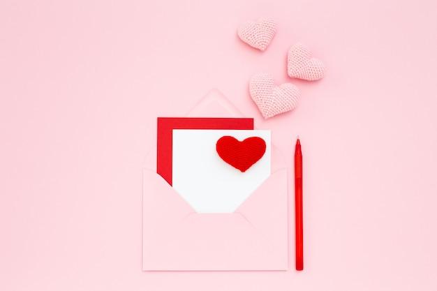 Открытка на день святого валентина, красные сердечки ручной работы в конверте на розовом фоне