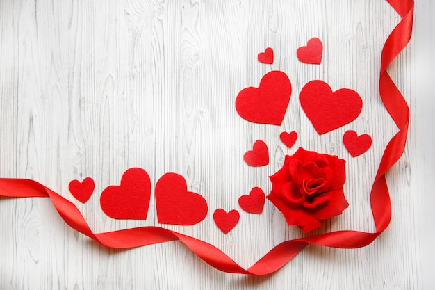 Valentine's day card, red hearts, ribbon and red rose on a white wooden background. space for text