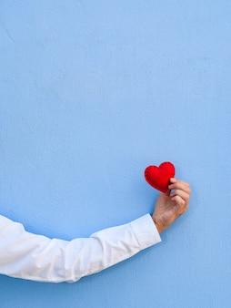 Валентинка. красное сердце в руке парня на фоне синей стены.