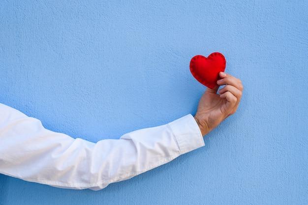 Валентинка. красное сердце в руке парня у синей стены