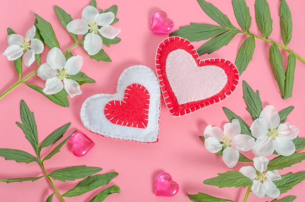 Valentine's day card, two hearts with a frame of flowers and leaves on a pink background