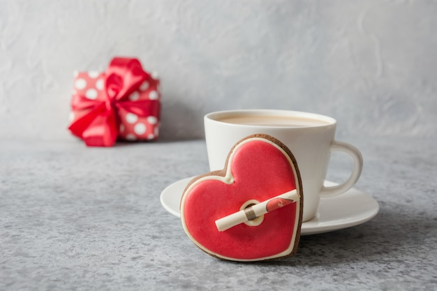 Valentine's day card. white cup of latte coffee with milk, gift and red heart cookies on grey. close up.