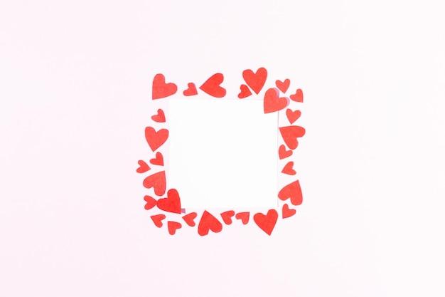 ピンクの背景に赤いボール紙のハートで囲まれたノートのバレンタインデーカード白い正方形