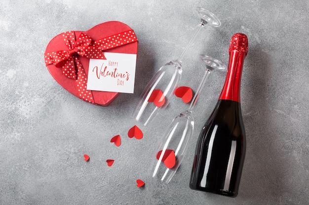 Открытка на день святого валентина с бутылкой шампанского, бокалы с коробкой конфет в форме сердца.