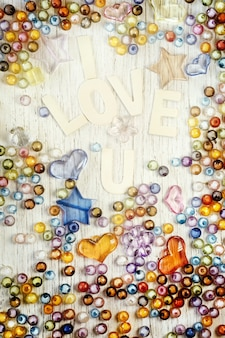 Valentine's day card with i love u text and heap of beads on wooden, sweet pastel color toned.