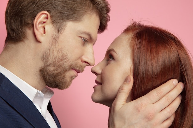 Valentine's day celebration, close up of caucasian couple's kissing and smiling on coral studio background. concept of human emotions, facial expression, love, relations, romantic holidays.