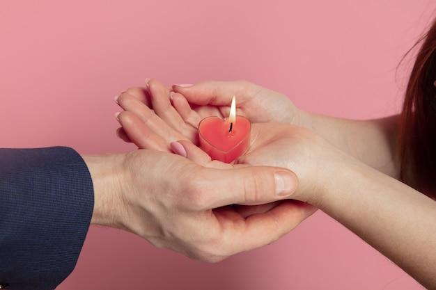 バレンタインデーのお祝い、珊瑚の背景にハート型のキャンドルを持っている白人カップルの手のクローズアップ。人間の感情、顔の表情、愛、関係、ロマンチックな休日の概念。