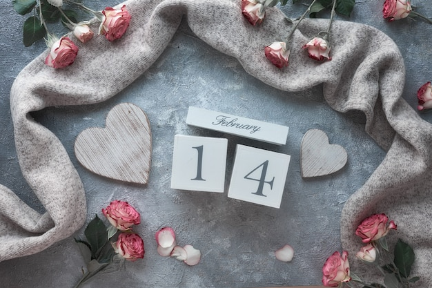 Valentine's day celebration, flat lay with wooden calendar, pink roses and wooden hearts on dark grey background.