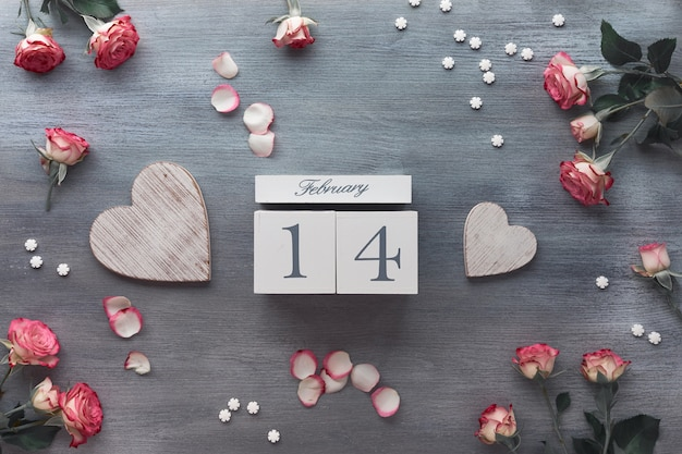 Valentine's day celebration, flat lay with wooden calendar, pink roses and wooden hearts on dark