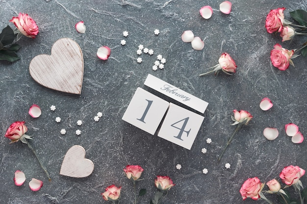 Valentine's day celebration, flat lay with wooden calendar, pink roses and wooden hearts