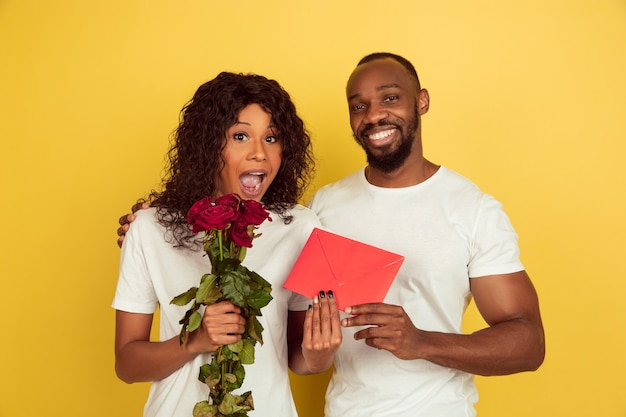 Celebrazione di san valentino, felice coppia afro-americana isolata su giallo
