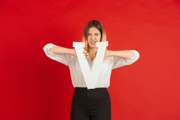 バレンタインデーのお祝い、赤い背景の上の手紙を保持している幸せな白人の女の子
