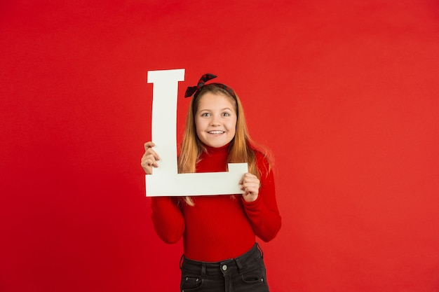 Valentine's day celebration, happy caucasian girl holding letter on red background