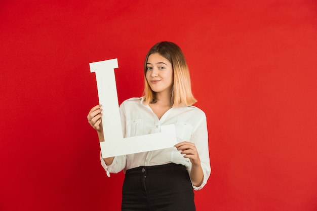 Valentine's day celebration, happy, cute caucasian girl holding letter on red studio