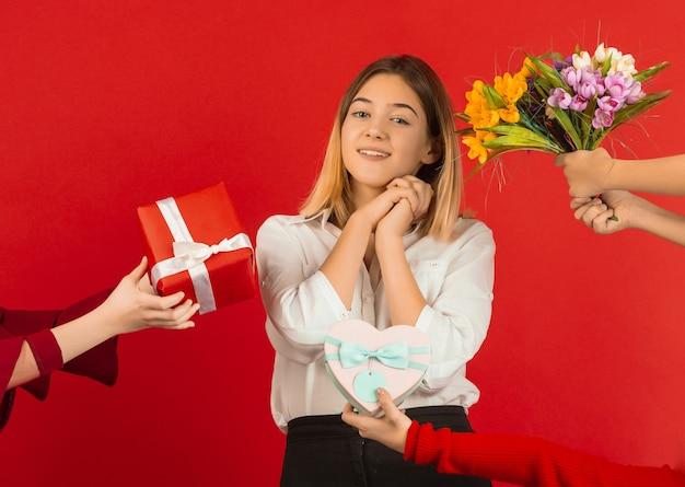 バレンタインデーのお祝い。幸せな、かわいい白人の女の子が赤いスタジオの背景に分離されました。