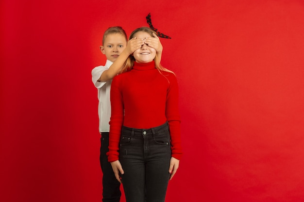 バレンタインデーのお祝い、赤いスタジオで隔離の幸せでかわいい白人の子供たち