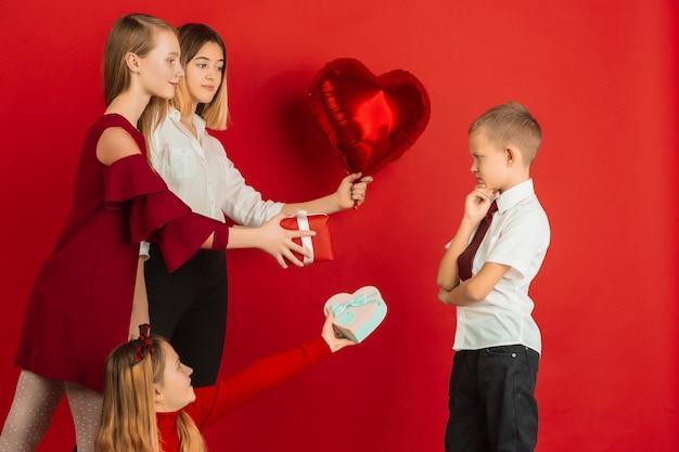 バレンタインデーのお祝い。幸せな、かわいい白人の十代の若者たちが赤いスタジオの背景に分離されました。