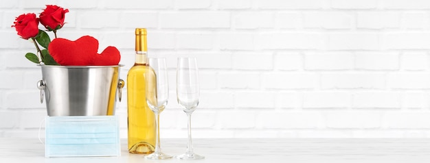Празднование дня святого валентина с вином, букетом и концепцией защиты лица в это тяжелое время.