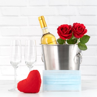 Valentine's day celebration with wine, bouquet and face mask protection concept during this hard time.