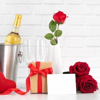Празднование дня святого валентина с вином, подарком и букетом роз для праздничного приветствия.