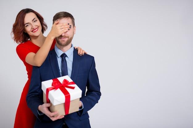 День святого валентина, рождество или сюрприз концепция - женщина удивляет своего парня подарком и копией пространства на белом фоне