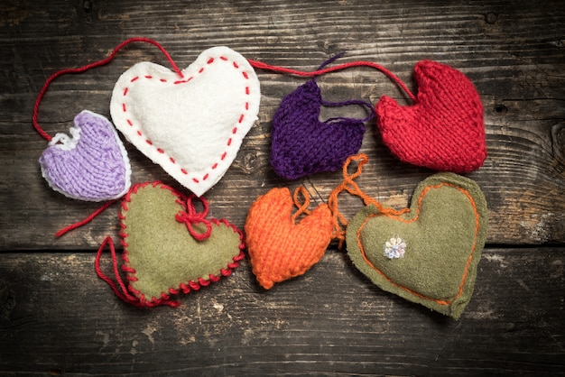 Valentine's day. colorful knitted hearts. red heart on the dark old boards.