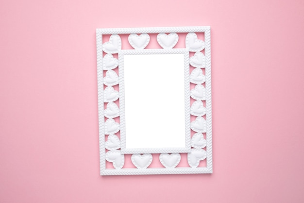 Valentine's day composition. photo frame with hearts on pastel pink background. wedding. birthday. happy woman's day. mothers day. flat lay, top view, copy space