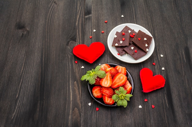 Valentine's day composition with chocolate, fresh ripe strawberries and red textile hearts