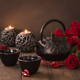 Valentine's day composition with green tea, black teapot, candles and roses on wooden table. valentines day greeting card concept with copy space